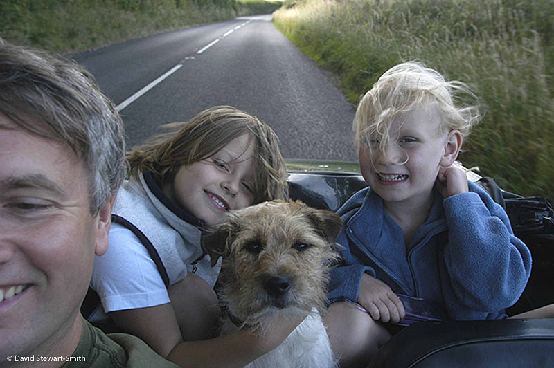 David and his two children with a dog driving in a car down a country lane in the summer. Somerset 2007