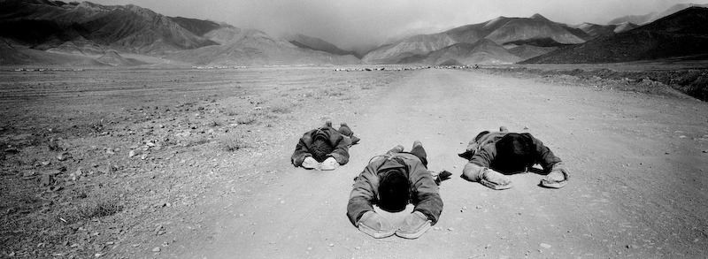 Buddhist pilgrims prostrate towards Lhasa. Some travel for months bowing and crawling their way to Lhasa, Tibet